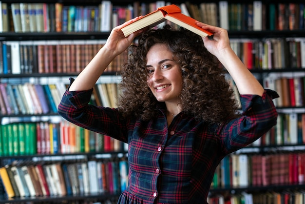 Playful curly brunette girl holding a book over her head and looking at the camera.