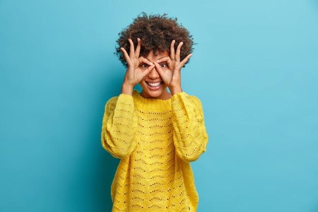 장난기 많은 곱슬 머리 여자는 재미 있고 손가락 안경을 광범위하게 미소 짓게합니다. 흰 이빨이 있습니다. 노란색 스웨터를 입고 노란색 스웨터를 입고 파란색 벽에 서