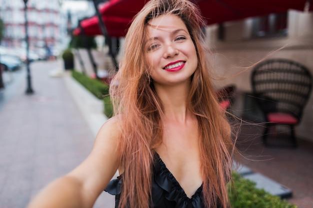 Игривый милый красный слышит женщину с улыбкой, делая автопортрет и наслаждаясь летними каникулами в европе. положительный внешний вид. черное платье, красные губы.