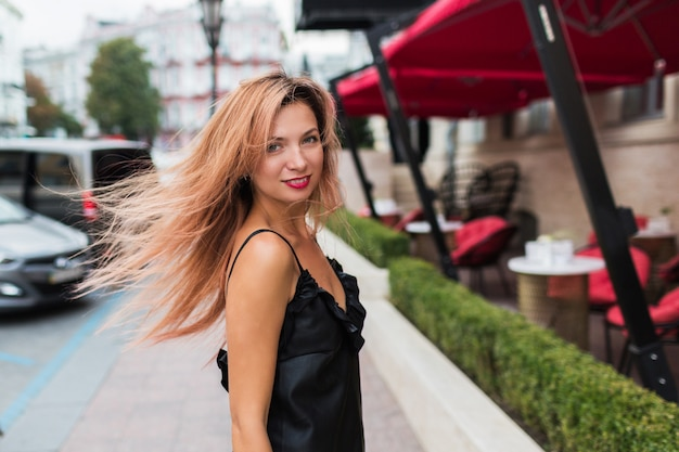 Playful cute  red hears woman with  smiling  making self portrait  and enjoying summer vacation in europe. positive outdoor image. black dress, red lips.
