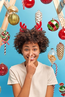 Playful dark skinned woman touches nose and smiles happily wears casual white t shirt prepares for festive event ready to celebrate merry christmas