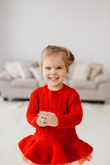 Игривая энергичная маленькая девочка позирует в студии