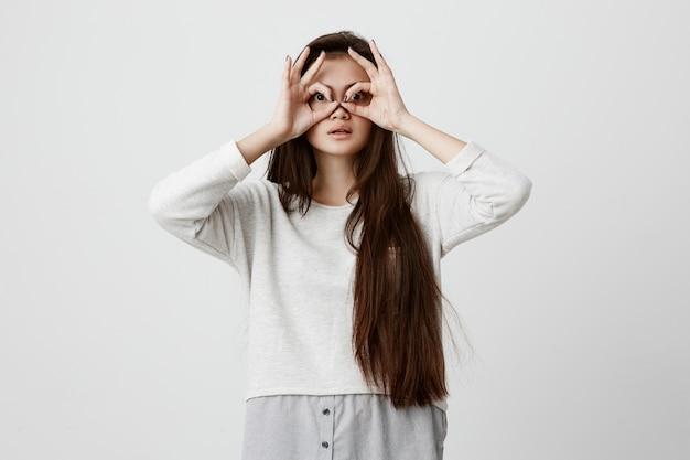 Игривая взволнованная девочка-подросток с темными длинными волосами, показывающая жестами ok обеими руками, притворяясь, что носит очки, с удивлением увидела что-то удивительное. эмоции, язык тела и жесты