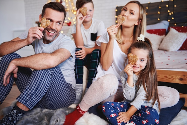 Famiglia allegra che celebra il natale a letto