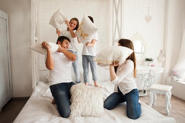 面白い枕を持っている遊び心のある家族がベッドの上で戦う