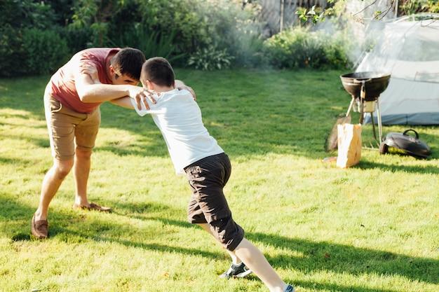 장난 아버지와 아들 공원에서 잔디에 싸우는