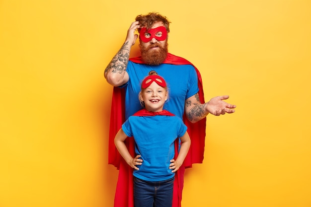 Playful father with small daughter wear superhero costumes, play together at home
