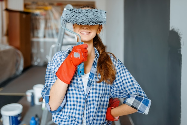 Playful female house painter covers her eyes with roller. home repair, happy woman doing appartment renovation, room decoration renovating