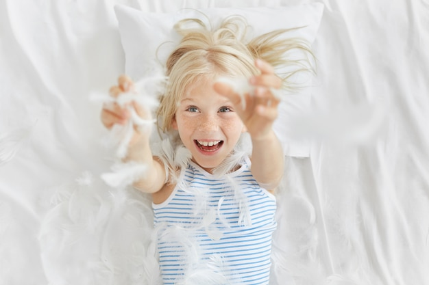 Playful freckled adorable girl with blue eyes, cathing feathers after tearing into pieces pillow, having fun before going to kindergarten. small girl playing with feathers on white bedclothes.