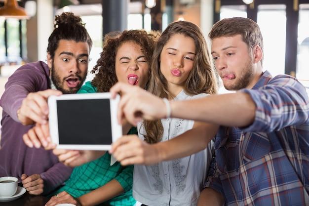 Игривые друзья делают селфи на цифровом планшете