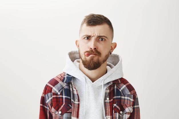 Игривый смешной бородатый парень показывает язык и гримасничает