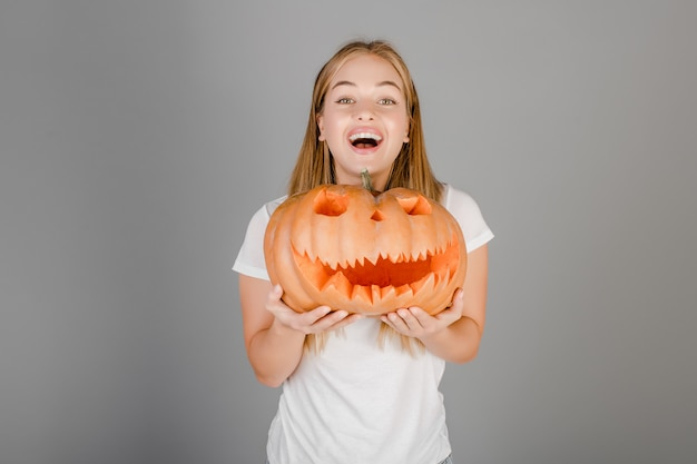 Playful funny blonde girl with halloween jack o lantern pumpkin isolated over grey