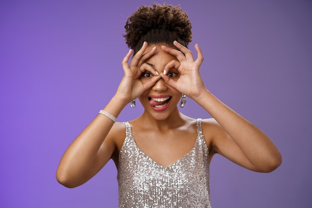 Playful funny good-looking african woman in afro hairstyle in silver glittering dress having fun show tongue smiling broadly make okay ok gesture on eyes look excited, standing blue background.