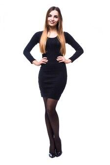 Игривая смешная женщина, стоящая в черном платье на белом в полный рост