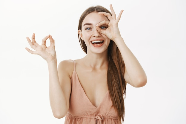 Playful gentle european female in beige trendy dress making okay gesture over eye and peeing through hole in fingers smiling joyfully having fun and spending time amused over gray wall