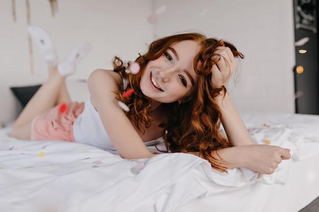 성실한 미소로 침대에서 포즈 장난 생강 여성 모델. 그녀의 침실에서 웃 고 debonair 백인 여자의 실내 샷.