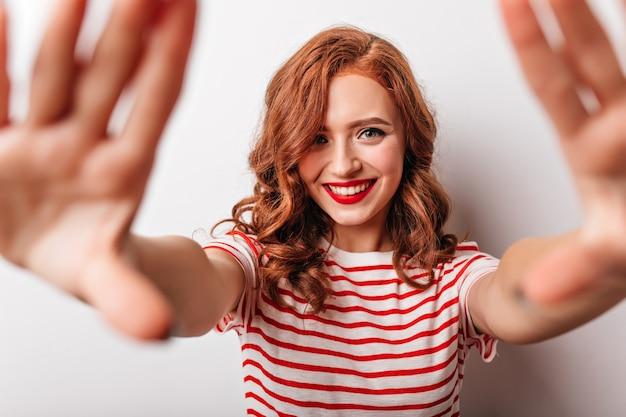 白い壁に喜んでポーズをとる遊び心のある生姜の女の子。笑顔の縞模様のtシャツの見事な白人女性