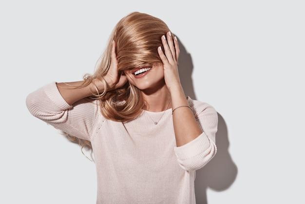 Игривая девочка. красивая молодая женщина закрыла лицо волосами и улыбнулась