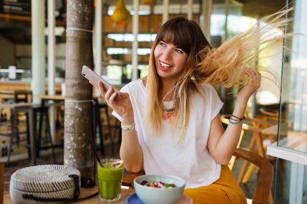 Ragazza allegra che gode della prima colazione saporita durante le vacanze in caffè moderno alla moda.