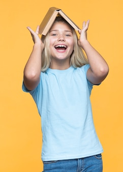 Playful girl holding book on head
