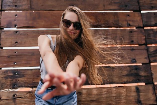 木製の壁で楽しんでいる黒いメガネの遊び心のある女の子。春に冷えるジーンズの魅力的な白人モデルの屋外ショット。