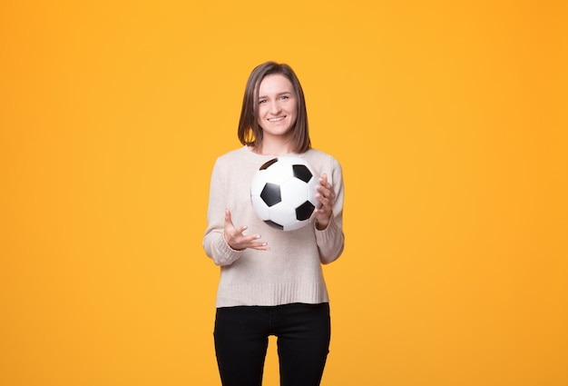 Playful girl is holding a ball.