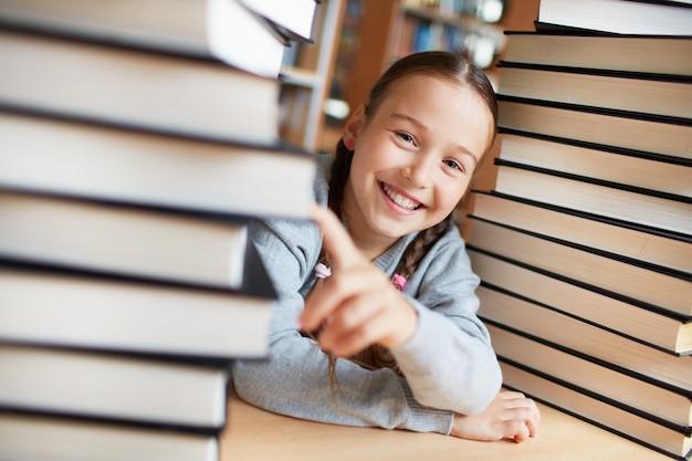 Игривая девушка с книгами в библиотеке