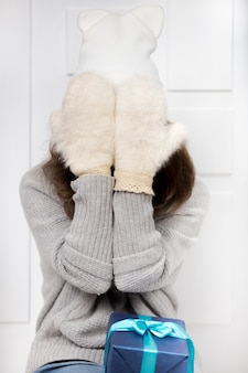 Playful girl with gloves covering her face