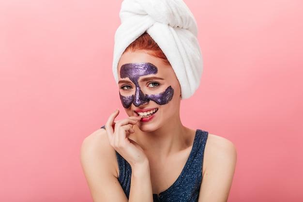분홍색 배경에 카메라를보고 머리에 수건으로 장난 소녀. 얼굴 마스크와 매력적인 백인 여자의 스튜디오 샷.