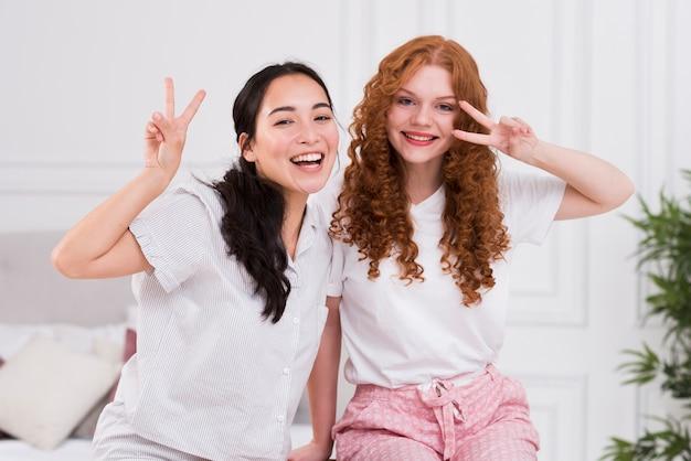 Playful girlfriends in pijamas at home