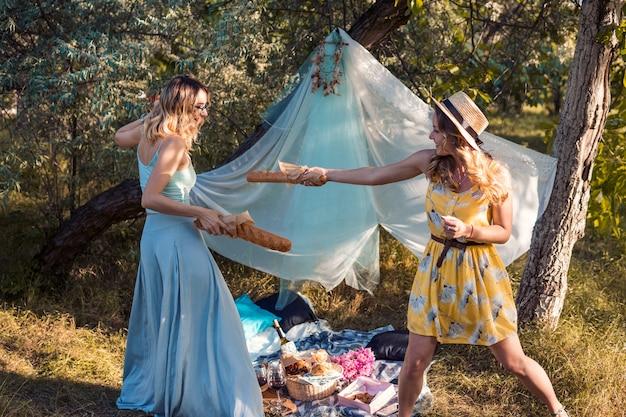 야외에서 피크닉을 만드는 빵 바게트와 싸우는 장난기 많은 소녀들. 처녀 파티