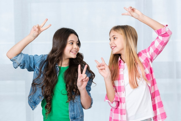 Playful girls showing peace sign