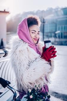 遊び心のある一瞥。両手でカップを持ちながら笑顔を保つ魅力的な女性