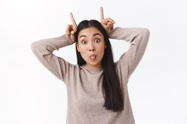 길고 건강한 검은 머리를 가진 장난기 많은 아시아 소녀, 머리에 뿔을 만들고 즐겁게 눈을 튀기고, 혀를 붙이고, 재미없고 열정적이며, 흰 벽에 서 있는 어린애