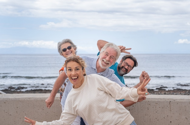 Игривая группа представителей разных поколений, глядя в камеру, шутит на открытом воздухе у моря