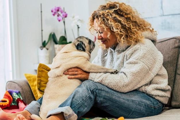 인간의 여자 사람과 소파에 키스하는 재미있는 퍼그 개와 함께 집에서 쾌활한 행복 활동