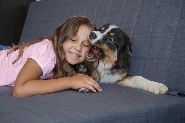 遊び心のある幸せなオーストラリアンシェパードの3色の子犬の犬の横になっている所有者の魅力的な小学生の白人の女の子と遊びます。