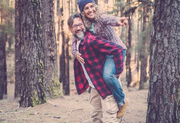 森の中のトレイルを歩きながらピギーバックを持っている遊び心のある幸せなハンサムな白人カップル。自然の概念の冒険-若い大人の男性と女性が一緒にアウトドアレジャーを楽しむ