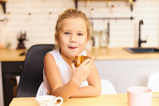 ダイニングテーブルにマグカップとおいしいクッキーを食べて居心地の良いキッチンに座っている遊び心のある幸せな少女。喜びと楽しさで焼きたての甘いパイを噛むかわいい面白い白人の赤ちゃん