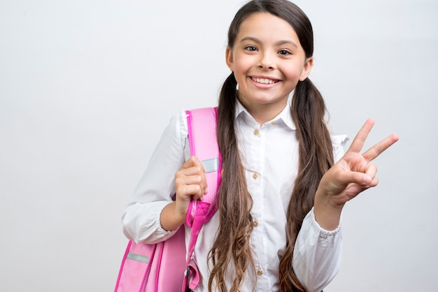 Playful hispanic schoolgirl carrying backpack on shoulder