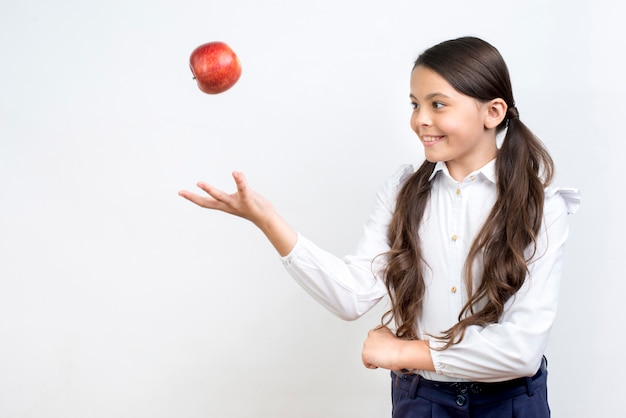 Playful hispanic schoolgirl tossing apple