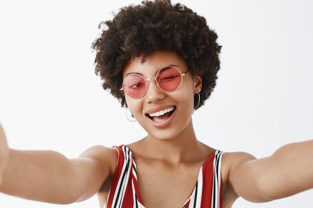 Giocoso afroamericano caldo con acconciatura afro, tirando le mani verso per fare selfie, ammiccando con gioia e sorridendo ampiamente, facendo una nuova foto del profilo per il social network