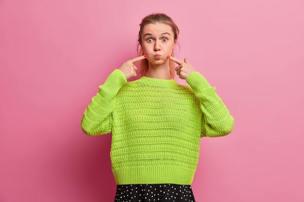 Giocosa e gioiosa ragazza europea fa una faccia buffa, trattiene il respiro, colpisce le guance con le dita per soffiare aria, indossa un maglione lavorato a maglia sciolto luminoso, si diverte