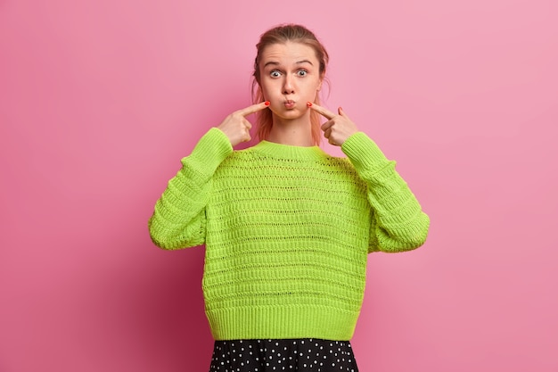 Игривая жизнерадостная европейка корчит рожицу, задерживает дыхание, тычет пальцами по щекам, чтобы дуть воздухом, носит яркий свободный вязаный свитер, веселится