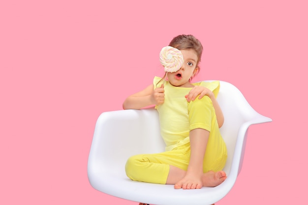 Playful kid with lollipop on chair