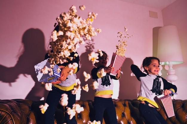 Playful kids throwing popcorn at home