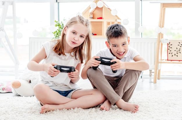 Playful kids with joysticks for gaming