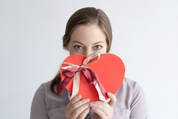 Playful lady holding heart shaped gift box in front of mouth