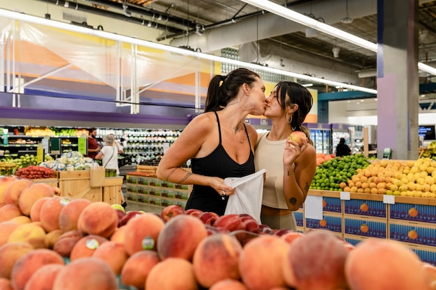 Playful lesbian couple shopping, kissing at a supermarket
