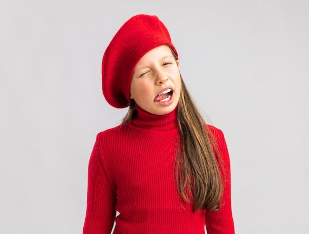 Bimba bionda allegra che indossa un berretto rosso che guarda la telecamera che mostra la lingua che fa l'occhiolino isolata sul muro bianco con spazio di copia